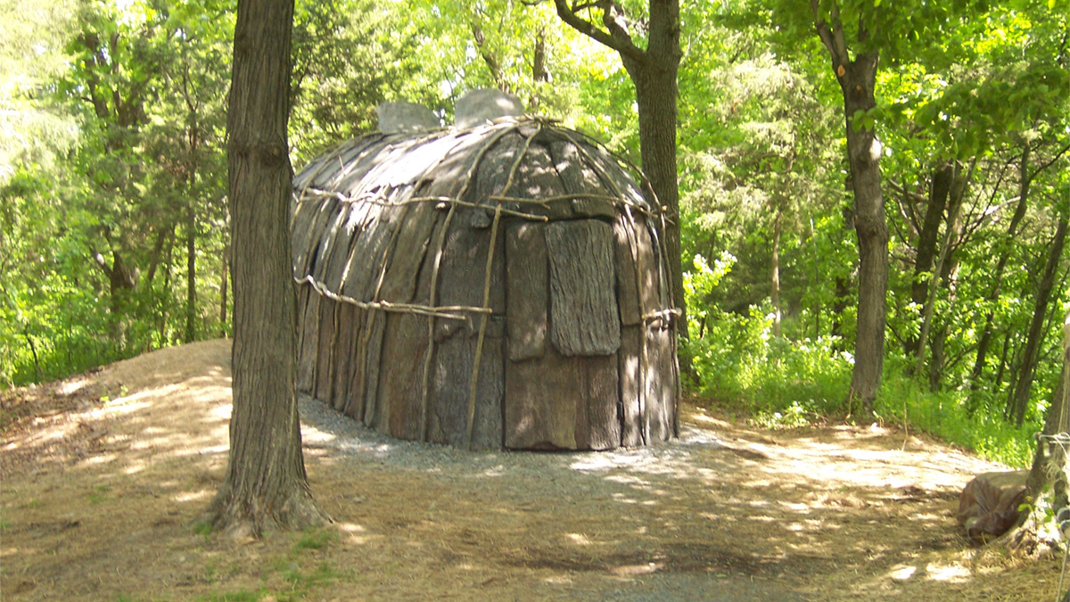 A replica Lenape longhouse sits between in a clearing in the forest