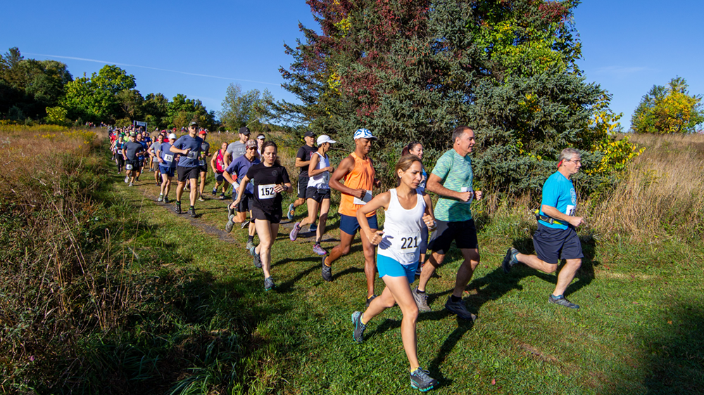 Runners moving toward the camera on a mowed path, with the race start line in the background.