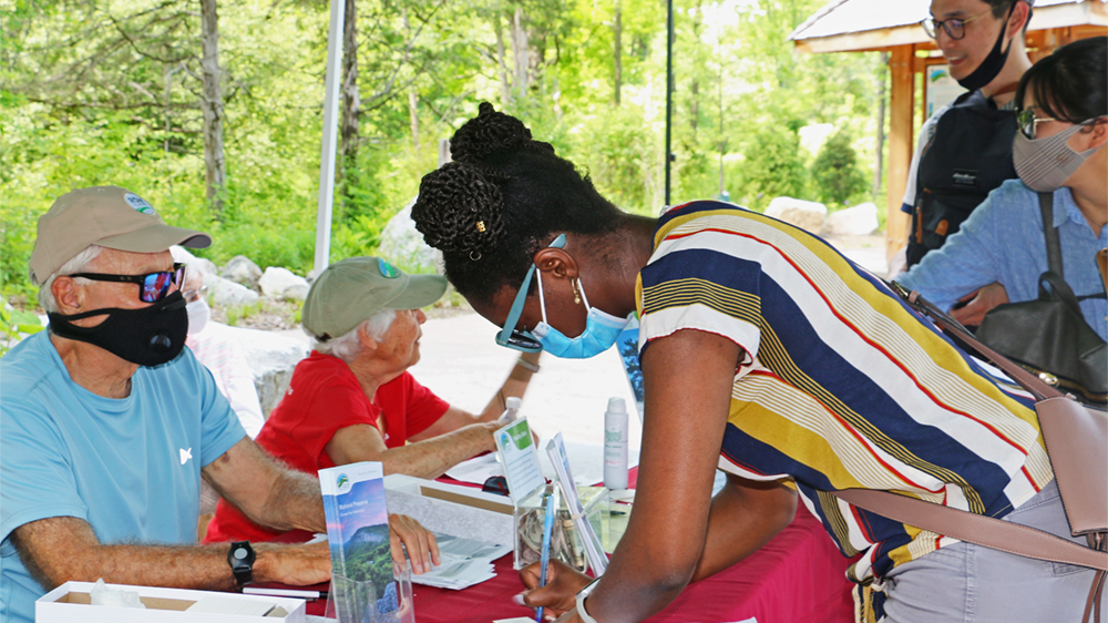 A visitor leans on a table to sign up for a Healthy Ulster pass. Sitting behind the table, a volunteer looks on.