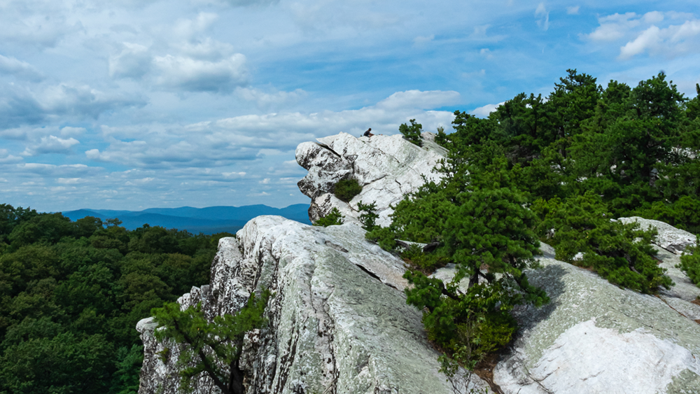 A vista featuring the top of Bonticou Crag with the Catskill mountains in the background. A hiker sits on top of the crag.